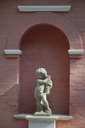 Angelot en pierre reconstituée portant une grappe de raisin - Hauteur 90 cm